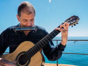 Martí Batalla tocando la guitarra y armónica.