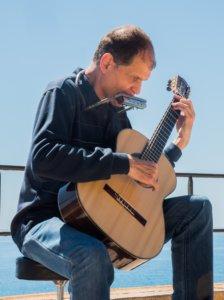 Martí Batalla de perfil tocando la guitarra y armónica.