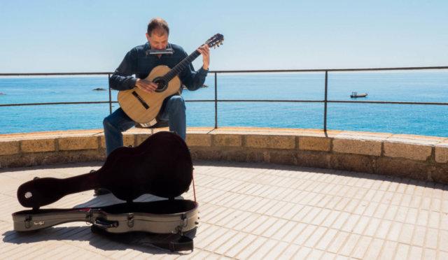 Martí Batalla tocando la guitarra y armónica en un mirador con vistas al mar.