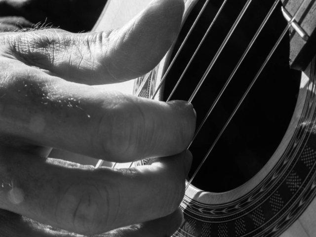 Foto en blanco y negro. Primer plano de la mano de Martí Batalla tocando la guitarra.