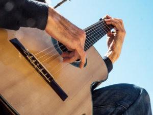 Primer plano de la guitarra y las manos de Martí Batalla vistas desde abajo.