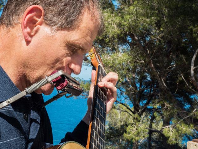 Martí Batalla tocando la guitarra y armónica con pinos detrás que dejan ver el mar a través de sus ramas.