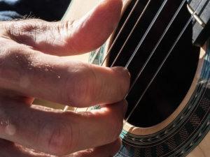Primer plano de los dedos de Martí Batalla pulsando las cuerdas de su guitarra.