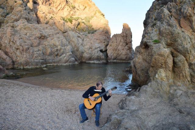 Martí Batalla tocando la guitarra y armónica al borde de la cala de Tossa.