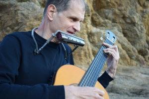 Martí Batalla visto en primer plano tocando la guitarra y la armónica.