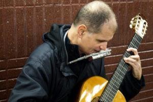 Primer plano de Martí Batalla tocando la guitarra y armónica en el metro de Barcelona.
