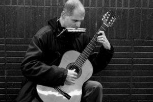 Martí Batalla tocando la guitarra y armónica en el metro de Barcelona