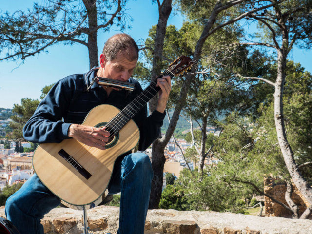 Martí Batalla playing guitar and harmonica with Tossa de Mar in the background.