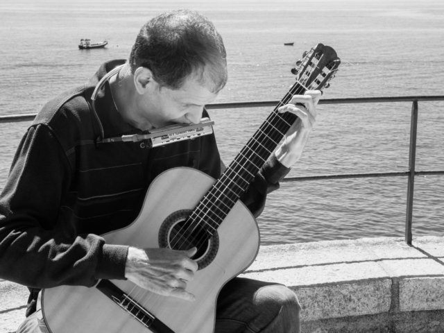Black and white photo of Martí Batalla playing the guitar and the harmonica with the sea in the background.