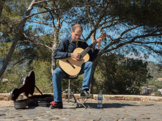Martí Battle playing the guitar and harmonica with a pine forest in the background.