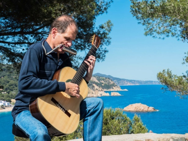 Martí Batalla playing the guitar and harmonica with the cove of Tossa de Mar in the background.