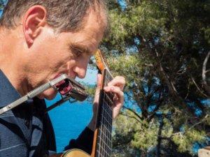 Martí Batalla tocant la guitarra i harmònica amb pins al darrera que deixen veure el mar a través de les seves branques.