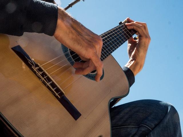 Primer pla de la guitarra i les mans de Martí Batalla vistes des de baix.