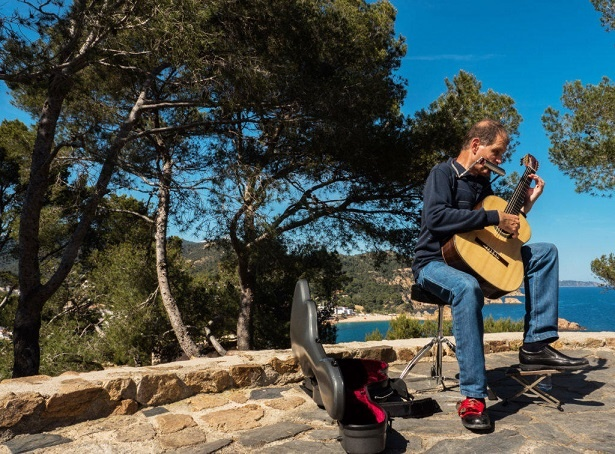 Martí Batalla in profile playing the guitar and harmonica in a viewpoint with the cove of Tossa de Mar in the background.