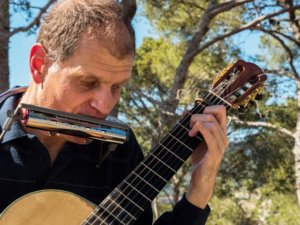 Close-up of Martí Batalla playing the guitar and harmonica with pine trees in the background.