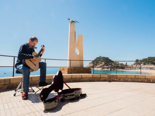 Martí Batalla in profile playing the guitar and harmonica next to the Albatross Monument in the Tossa de Mar viewpoint.