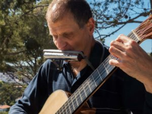 Close-up of Martí Batalla playing guitar and harmonica.